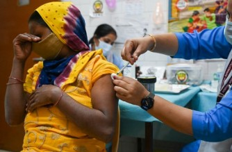A health worker inoculates a woman with a dose of the Covaxin vaccine against the Covid-19 coronavirus at a health centre in New Delhi on October 21, 2021. - India administered its billionth Covid-19 vaccine dose on October 21, according to the health ministry, half a year after a devastating surge in cases brought the health system close to collapse. (Photo by Prakash SINGH / AFP)