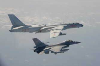 """(FILES) This file handout photo taken and released on February 10, 2020 by Taiwan's Defence Ministry shows a Taiwanese F-16 fighter jet flying next to a Chinese H-6 bomber (top) off the coast of Taiwan. - Chinese fighter jets and bombers now routinely surface on Taiwan's radar screens, the latest aggressive tactic to pile pressure on the democratic island as fears rise that one mistake could suddenly spark a war. (Photo by Handout / Taiwan's Defence Ministry / AFP) / TO GO WITH Taiwan-China-politics-military-US,FOCUS by Amber Wang and Jerome Taylor RESTRICTED TO EDITORIAL USE - MANDATORY CREDIT """"AFP PHOTO / Taiwan's Defence Ministry """" - NO MARKETING NO ADVERTISING CAMPAIGNS - DISTRIBUTED AS A SERVICE TO CLIENTS"""