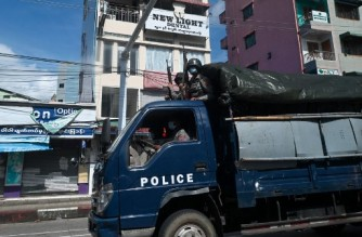 Police patrol in a truck in downtown Yangon on October 22, 2021. (Photo by AFP)