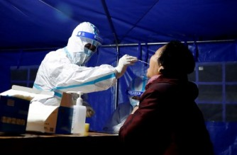 This photo taken on October 21, 2021 shows a resident undergoing a nucleic acid test for the Covid-19 coronavirus in Zhangye in China's northwestern Gansu province. (Photo by AFP) / China OUT