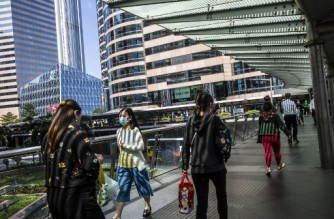 People walk on a foot bridge in the Central district of Hong Kong on October 25, 2021. (Photo by ISAAC LAWRENCE / AFP)