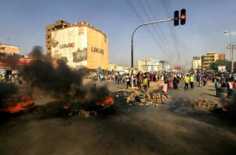 """Sudanese protesters use bricks and burning tyres to block 60th Street in the capital Khartoum, to denounce overnight detentions by the army of members of Sudan's government, on October 25, 2021. - Armed forces detained Sudan's Prime Minister over his refusal to support their """"coup"""", the information ministry said, after weeks of tensions between military and civilian figures who shared power since the ouster of autocrat Omar al-Bashir. (Photo by AFP)"""