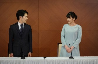 Japan's former princess Mako (R), the elder daughter of Prince Akishino and Princess Kiko, and her husband Kei Komuro (L), who she originally met while at university, pose at the start of a press conference to announce their marriage registration, at the Grand Arc Hotel in Tokyo on October 26, 2021. (Photo by Nicolas Datiche / POOL / AFP)
