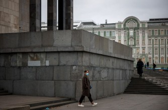 A woman wearing a protective face mask walks in Moscow on October 27, 2021. - Russia reported on October 23, 2021 a record 1,075 Covid-19 deaths in 24 hours as Europe's hardest hit country with dramatically low vaccination rates braces for nationwide curbs from next week. On October 27, 2021 authorities cautioned Russians against travelling during a non-working period to stem a spike in coronavirus infections and deaths. (Photo by Dimitar DILKOFF / AFP)