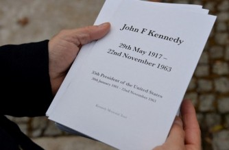 An attendee holds an order of service at a memorial for former US President John F Kennedy in Runnymede, Surrey on November 22, 2013, to mark the 50th anniversary of his assassination. AFP PHOTO / BEN STANSALL (Photo by BEN STANSALL / AFP)
